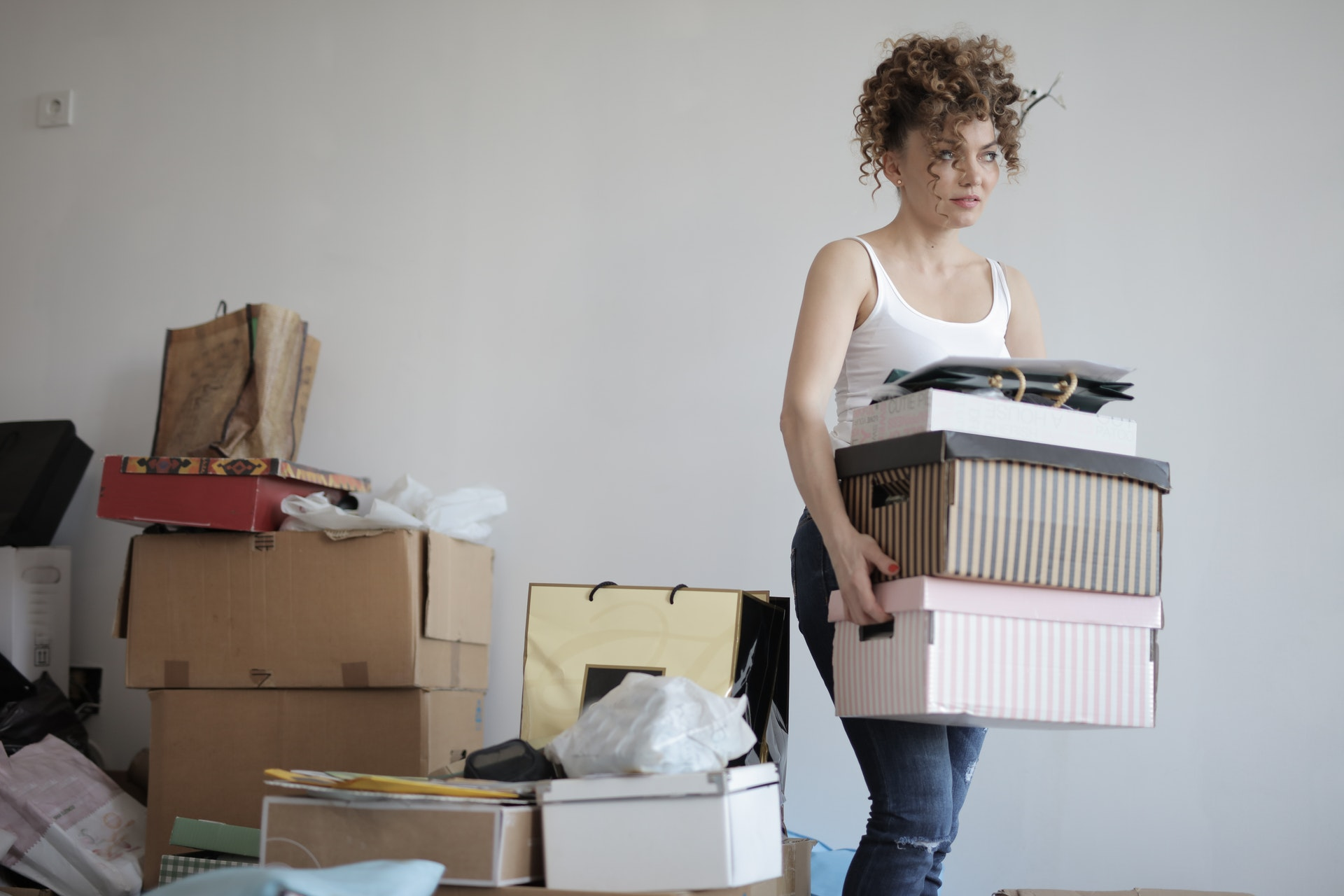 Woman carrying boxes with boxes in background