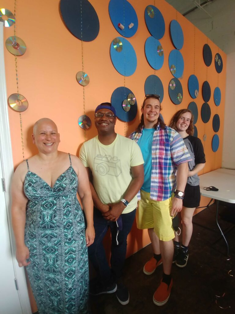 Image of four people smiling standing against an orange wall